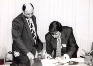 Denis Tardif signing the document transferring francophone school management in June 1994