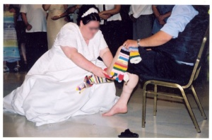 A bride putting the socks on the groom's unmarried older brother in preparation for his dance