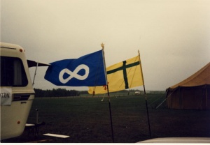 The Fransaskois Flag and the Métis Flag flying in the wind side by side during the 6th Fête Fransaskoise in Batoche in 1985.