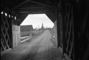 View of the inside of a Covered Bridge with a Bell-Tower in the distance