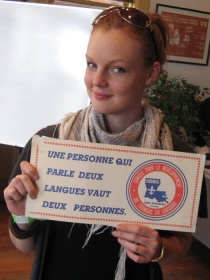 A young woman proudly displays a poster