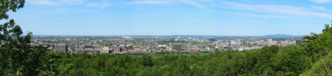 Panoramic view looking out over the east of Montreal, taken from Mont Royal. In the foreground the Mont-Royal Plateau. A bit further back, the Olympic Stadium with its 175-metre [574.1-foot] leaning tower. In the background, the Saint Lawrence River. July 2002.