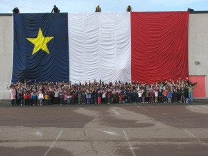 Schoolchildren posing proudly in front of a giant Acadian flag