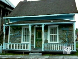 Arthur Villeneuve's home in its original location in Chicoutimi, in 1964. Still frame taken from a documentary on the artist produced by the NFB.