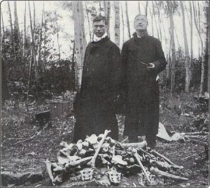 Father Arthur Béliveau and Judge Louis-Arthur Prud'homme standing behind bones discovered during the Société historique de Saint-Boniface expedition to Fort Saint-Charles in 1908