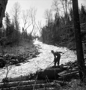 A log driver prevents a log jam in a waterway, Gatineau, 1942.