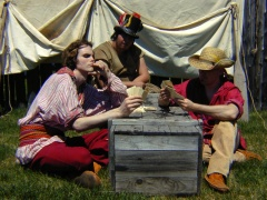 A group of interpreters in the role of voyageurs playing cards, Fort William.